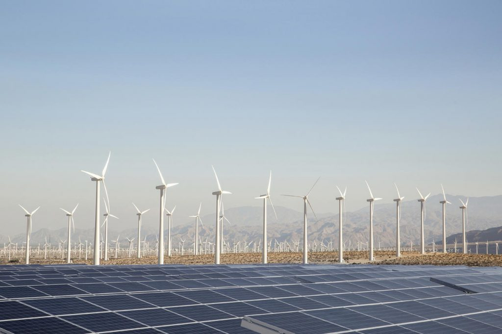 Many wind turbines and a large solar panel array in a desert valley, mountains in the distance and blue sky above. Palm Springs, California, USA